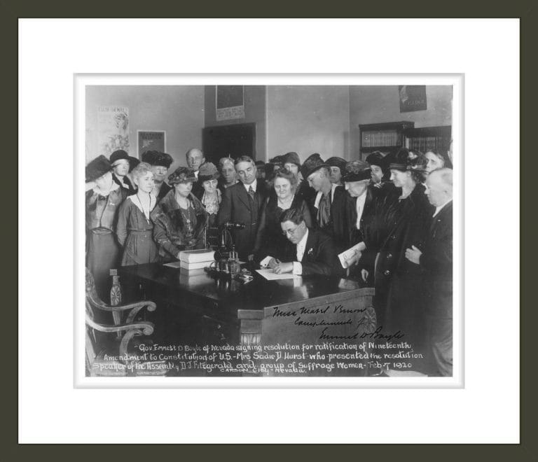 Gov[ernor] Emmett D. Boyle of Nevada signing resolution for ratification of Nineteenth Amendment to Constitution of U.S. - Mrs. Sadie D. Hurst who presented the resolution, Speaker of the Assembly D.J. Fitzgerald and group of Suffrage Women, Feb. 7, 1920, Carson City, Nevada