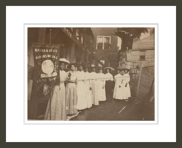 [Nine African-American women posed, standing, full length, with Nannie Burroughs holding banner reading,