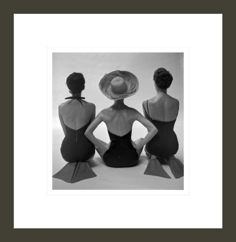 Back view of fashion models in swim suits, two kneeling wearing swim fins, and one seated